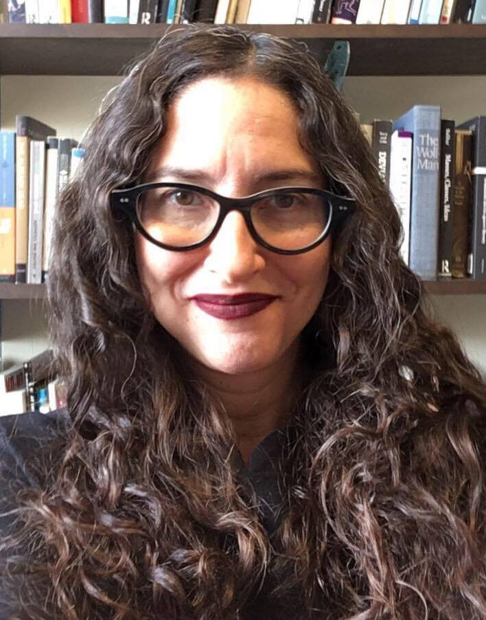 A headshot of Dana Seitler smiling slightly at the camera. She is a white woman with long dark brown curly hair and she wears black thick-rimmed glasses and matte burgundy lipstick. In the background are several shelves of books.
