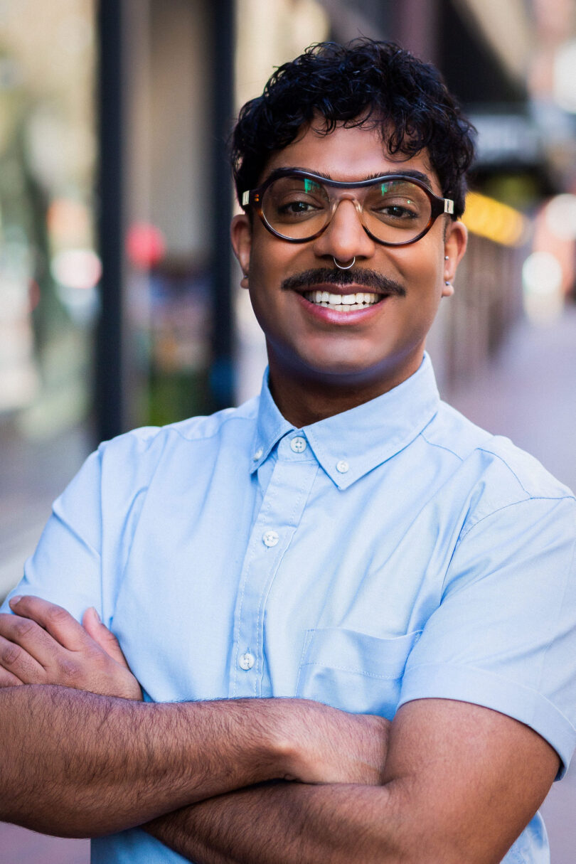 Portrait shot of Rahim Thawer smiles widely at the camera. He wears thick rimmed round glasses and a blue collared shirt. HIs arms are crossed.